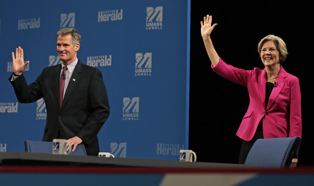 Republican U.S. Sen. Scott Brown, left, and Democratic challenger Elizabeth Warren wave to the audience prior to a debate sponsored by the Boston Herald at UMass Lowell, Monday, Oct. 1. (AP)