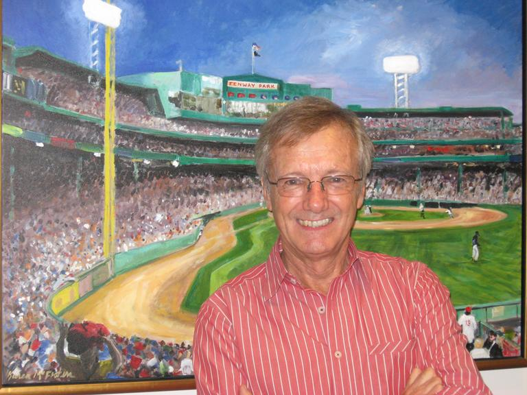 Tony Wheeler, posing in front of a painting of Boston's Fenway Park by Karen McFeaters, at WBUR. (Here & Now/Lynn Menegon)