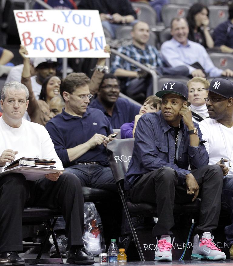 """Rapper Jay-Z, bottom right, who is part owner of the Nets, attends the team's final NBA basketball home game as the """"New Jersey Nets,"""" before the team packs up and move to Brooklyn. (AP/Julio Cortez)"""