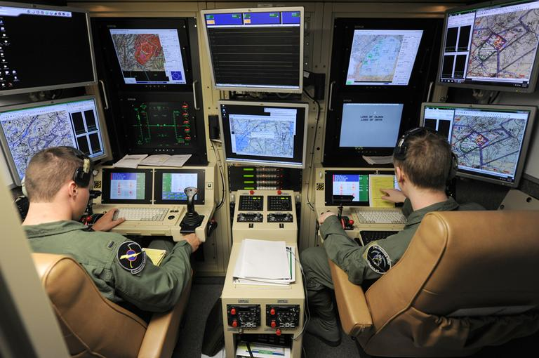 A student pilot and sensor operator man the controls of a MQ-9 Reaper in a ground-based cockpit during a training mission flown from Hancock Field Air National Guard Base in Syracuse, New York, in June. (AP/TSgt Ricky Best, Defense Department)