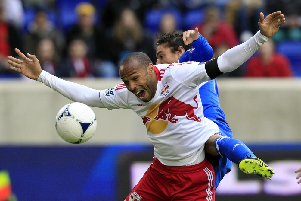 New York Red Bulls forward Thierry Henry is hit from behind by a Montreal Impact player during an MLS game in New Jersey. Henry is former Arsenal player and an international star. (Mel Evans/AP)