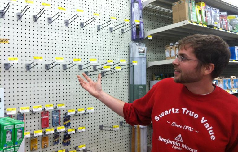 Salesperson Jeremy Perry, 27, shows the now-empty flashlight section at Swartz Hardware in Newton Monday. (Andrea Shea/WBUR)