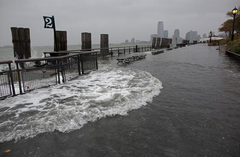 Waves wash over the seawall near high tide at Battery Park in New York on Monday. (Craig Ruttle/AP)