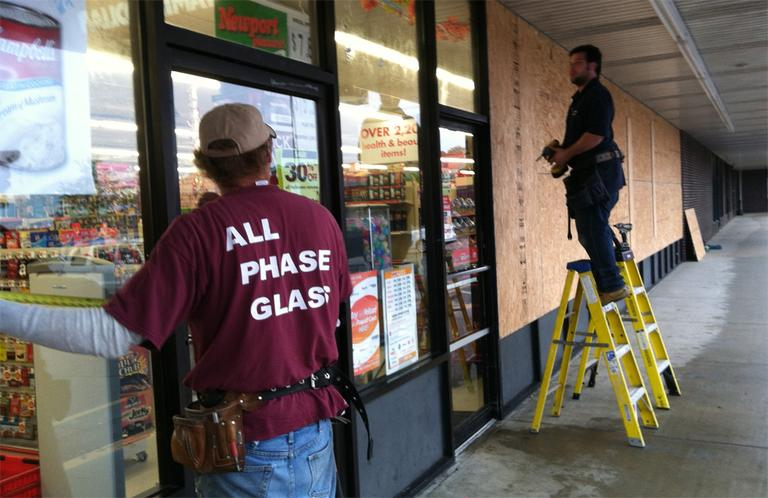 Barry Higginbottom, left, and Ryan Snyder board up a Family Dollar store near the Clark's Cove neighborhood in New Bedford on Monday. (Steve Brown/WBUR)