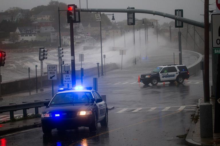 Revere police block Winthrop Parkway as waves crash against the sea wall there. (Jesse Costa/WBUR)