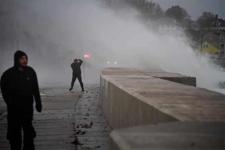 A bystander covers up from being hit with wind and a crashing wave on Winthrop beach Monday. (Jesse Costa/WBUR)