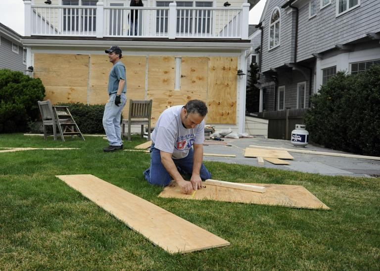 Jeff Babushkin, right, and Brad Purcell board up Purcell's home in Fairfield, Conn., Sunday, Oct. 28, 2012. (Jessica Hill/AP)