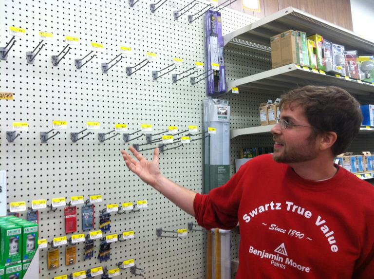Jeremy Perry shows the now-empty flashlight section at Swartz Hardware in Newton Monday. (Andrea Shea/WBUR)