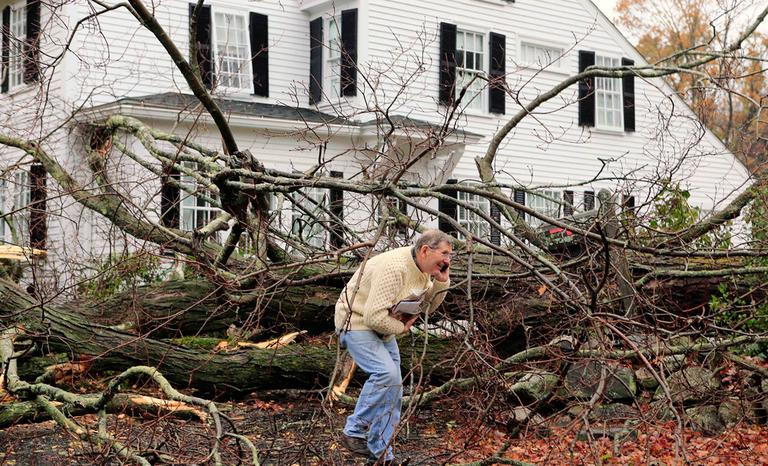 John Constantine makes his way out of his Andover house after winds from Sandy toppled a tree on Monday. (Winslow Townson/AP)