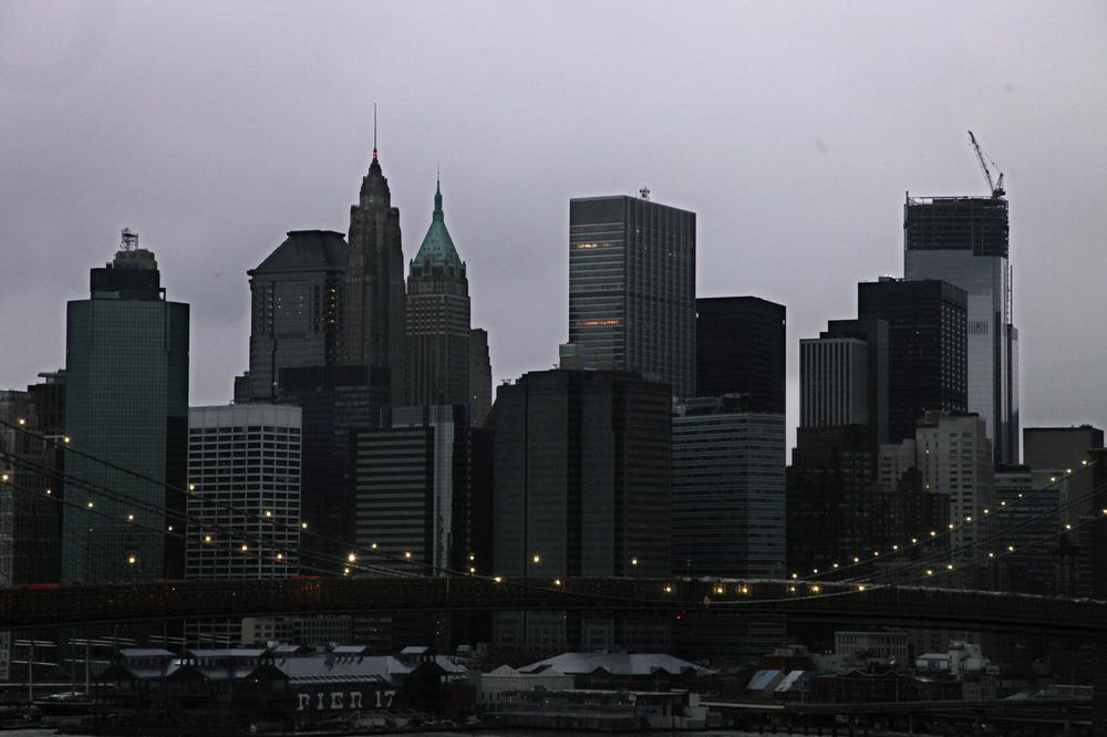 The lights on the Brooklyn Bridge stand in contrast to the lower Manhattan skyline which has lost its electrical supply on Tuesday. (Mark Lennihan/AP)