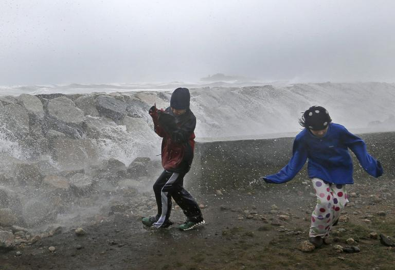 Youngsters run as waves crash against a seawall in Scituate on Monday. (Elise Amendola/AP)