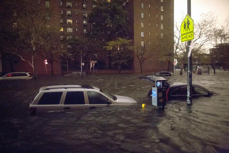 Vehicles are submerged on 14th Street near the Consolidated Edison power plant on Monday in New York. (John Minchillo/AP)
