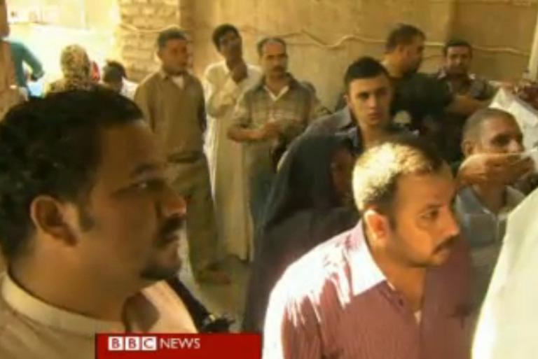 Iraqis who fled to Syria are now returning to Iraq to escape the bloodshed. In this screenshot from a BBC video, Iraqis line up for government grants. (BBC screenshot)