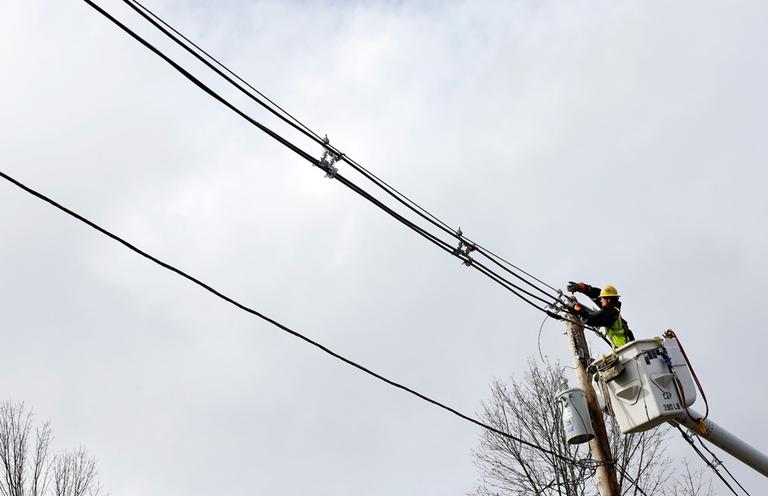 A utility crewmember works to restore power in Andover on Tuesday. (Elise Amendola/AP)