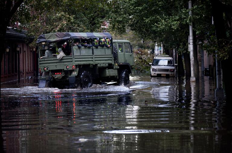 Members of the National Guard and Hoboken Police ride a large truck through floodwaters used to pluck people from high water in Hoboken, N.J., Wednesday, Oct. 31, 2012, in the wake of superstorm Sandy. Parts of the city are still covered in standing water, trapping some residents in their homes. (Craig Ruttle/AP)