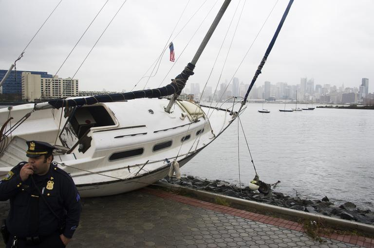 A boat rests on the waterfront of the Hudson River in Hoboken, N.J. across from New York City, background right, on Tuesday, after superstorm Sandy made landfall in New Jersey Monday evening. (Charles Sykes/AP)