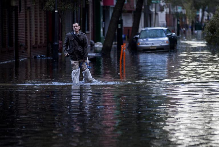 David Bagatelle, of Hoboken, N.J., walks from his residence on Park Avenue through high water in Hoboken, N.J., on Wednesday, in the wake of superstorm Sandy. Bagatelle's home is surrounded by water, but dry, where his wife and seven day old baby are staying. (Craig Ruttle/AP)