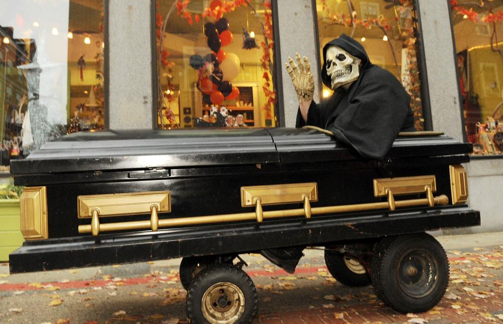 Frank Major, of Chicopee, dressed as the grim reaper rides in a motorized coffin days before Halloween in Salem in 2009. (AP)