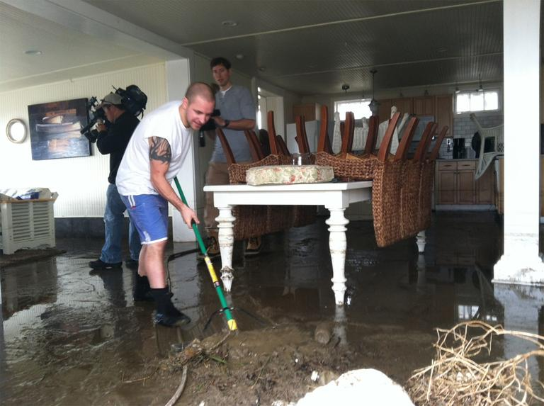 Jason Locke sweeps mud from his parents' home in Westport. (Fred Thys/WBUR)
