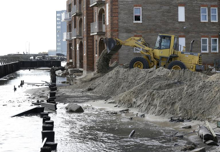 A worker uses a backhoe to move sand near a boardwalk that was destroyed by superstorm Sandy in Atlantic City, N.J., on Wednesday. (Patrick Semansky/AP)