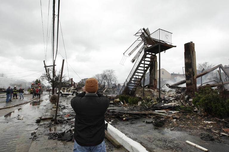 A man photographs damage caused by a fire in the Belle Harbor neighborhood in the New York City borough of Queens on Tuesday. (Frank Franklin II/AP)