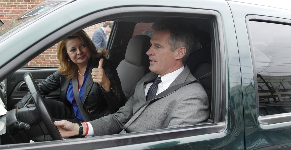 U.S. Sen. Scott Brown drives his truck as his wife Gail Huff gestures to supporters after a campaign stop in Watertown Oct. 24. (Charles Krupa/AP)