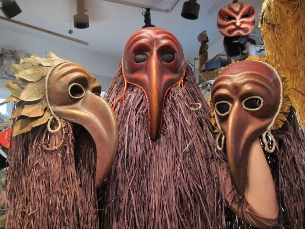 Studio assistant Anya Malkina holds up some masks. (Andrea Shea/WBUR)