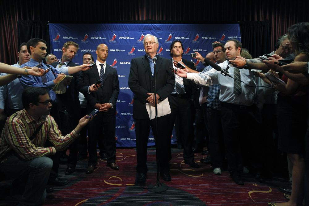 Reporters surround Donald Fehr, the executive director of the NHL Players' Association. Aside from continuing negotiations between the association and the NHL, sports reporters will have limited hockey content to cover in the next month. (Mary Altaffer/AP)