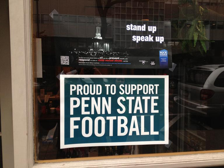 A common juxtaposition of signs in State College storefronts, one pledging support for the football team, the other for victims of sexual abuse. (Adam Ragusea/Georgia Public Broadcasting)