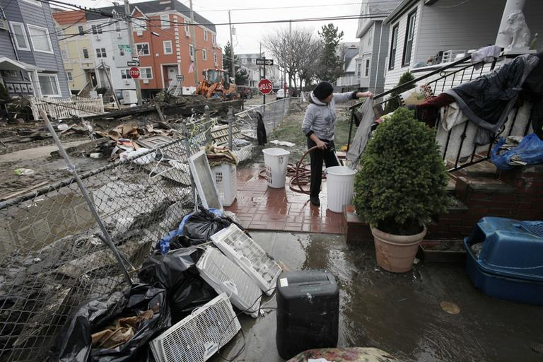 Ruth Dina Ticona washes the mud from clothing damaged by Superstorm Sandy in the front yard of her home in the oceanside community of Far Rockaway, New York, on Thursday. (Mark Lennihan/AP)