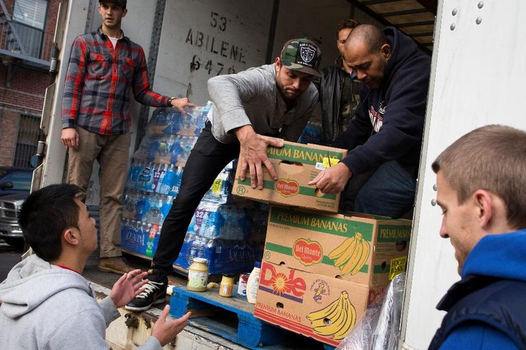 Volunteers help unload food from a truck on Friday, for distribution to the residents of the Lower East Side in Manhattan, New York. (John Minchillo/AP)