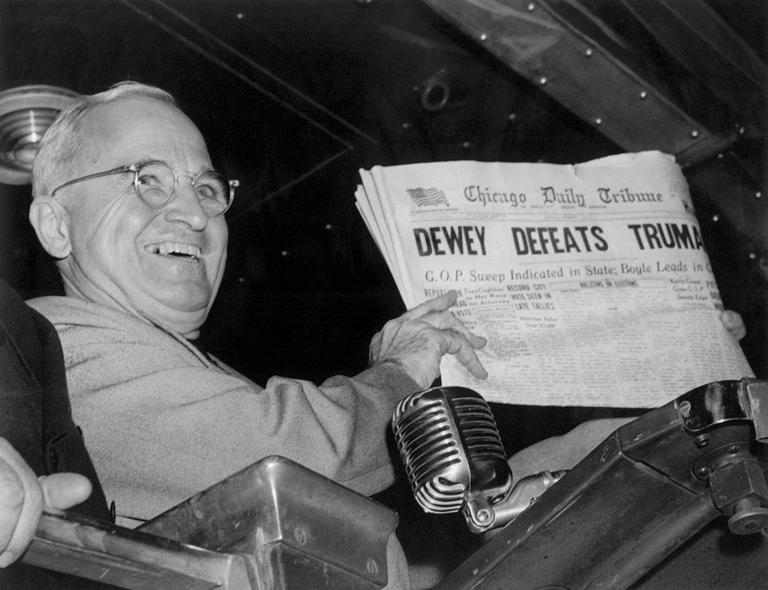 "In November 1948, President Harry S. Truman holds up an election day edition of the Chicago Daily Tribune, which, based on early results, mistakenly announced ""Dewey Defeats Truman."" (Byron Rollins/AP)"