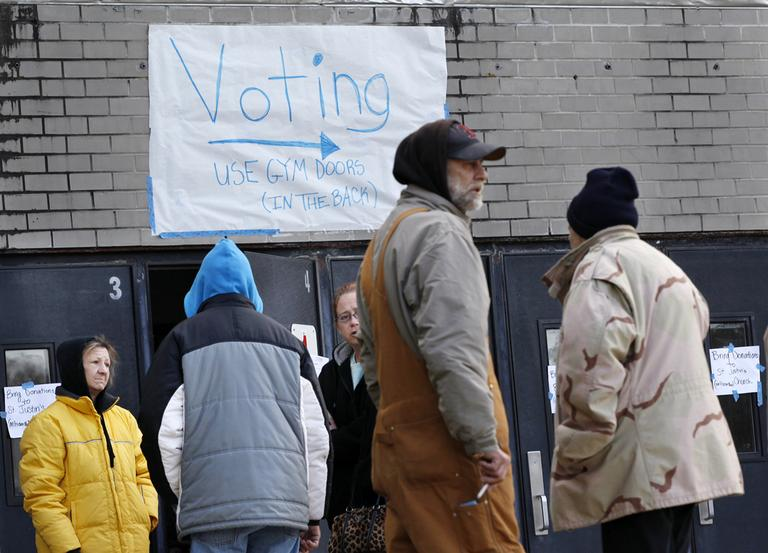 People, many displaced from the Jersey Shore by Superstorm Sandy, stand outside the shelter where they are staying at Toms River East High School on Tuesday, in Toms River, N.J. The school is also a polling station for elections. (Mel Evans/AP)
