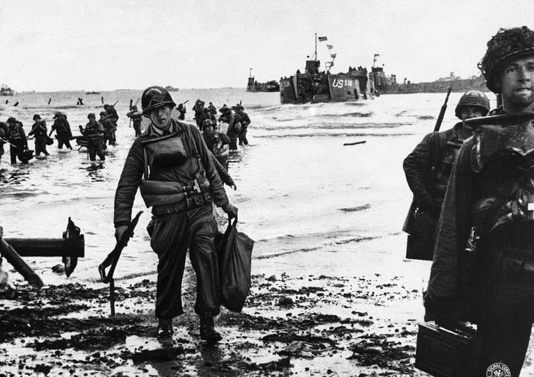U.S. assault troops, laden with equipment, wade through the surf to a Normandy beach from landing craft in June 1944 to support those who had gone before in the D-Day assault. (AP)