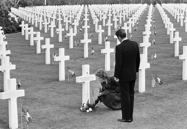 Nancy Reagan puts down a bunch of flowers at the grave of Theodore Roosevelt Jr. at the Normandy American Cemetery at Omaha Beach, France, as the Pres. Ronald Reagan stands behind her. (Bob Daugherty/AP)