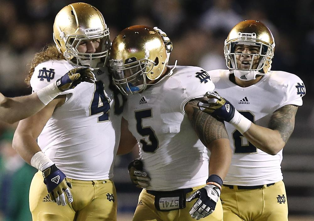 Teammates congratulate Notre Dame linebacker Manti Te'o for an interception during a game against Boston College. Notre Dame won 21-6 and are 10-0 this season. (Winslow Townson/AP)