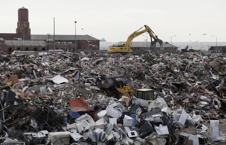 Pieces of construction equipment work on the pile of debris, collected during the cleanup from Superstorm Sandy, in the parking lot of Jacob Riis Park in the Rockaway section of the Queens borough of New York on Wednesday. (Mark Lennihan/AP)