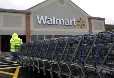 A worker pulls a line of shopping carts toward a Walmart store in North Kingstown, R.I. in November 2012. (Steven Senne/AP)