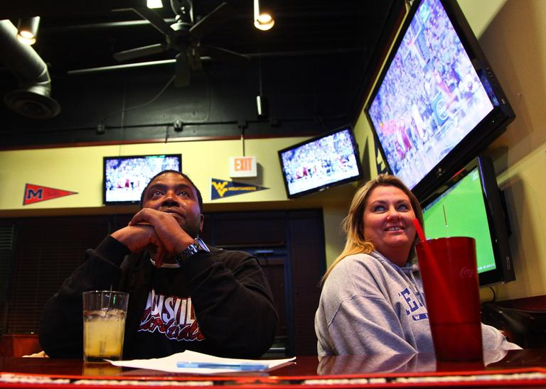 Damon Harris and Debbie Bailey are a couple divided. He's a Cardinal fan. She loves the Wildcats. On a Friday night, they watch UK stomp Lafayette College. (Anne Marshall/Only A Game)