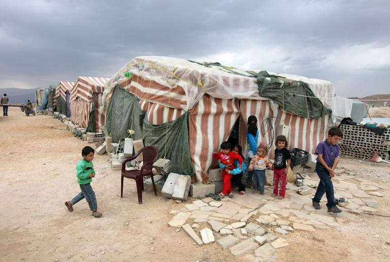 Syrian refugees children stand in front of their tents at a refugee camp last month in Arsal, a Sunni Muslim town eastern Lebanon near the Syrian border, that has become a safe haven for war-weary Syrian rebels and hundreds of refugee families. (Bilal Hussein/AP)