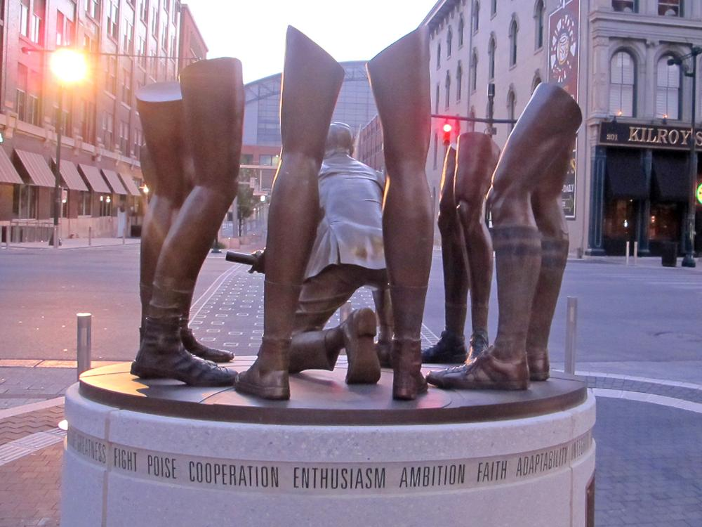 A kneeling John Wooden is surrounded by players — well, players' legs to be more accurate — in this sculpture in Indianapolis, Ind. (Bill Littlefield/Only A Game)