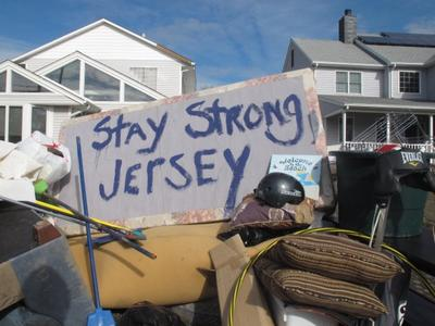 Residents of a flood-wrecked home in Point Pleasant Beach N.J. offer encouragement to fellow Superstorm Sandy victims. (AP Photo/Wayne Parry)