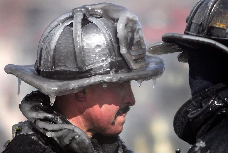 A firefighter's helmet is caked in ice at the scene of a four-alarm fire in Boston, Sunday, Feb. 12, 2012. Freezing temperatures and high wind hampered efforts to fight the blaze. (AP Photo/Michael Dwyer)