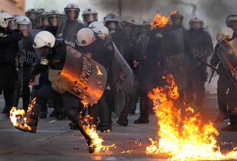 A riot police officers tries to extinguish flames from a petrol bomb thrown by protesters outside the Greek parliament, Athens, Sunday, Feb. 12, 2012. Tens of thousands of protesters gathered in the square outside Parliament. A few hundred anarchists started to throw bottles and firebombs at police, who responded with tear gas and stun grenades. (AP Photo/Thanassis Stavrakis)