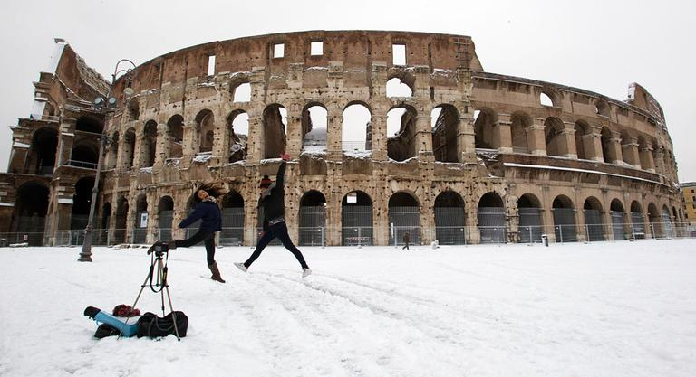 Two girls take a self-timer photo in front of a snow surrounded ancient Colosseum, in Rome Saturday, Feb. 4, 2012. A rare snowfall blanketed Rome on Friday, forcing the closure of the Colosseum over fears tourists would slip on the icy ruins, and leaving buses struggling to climb the city's slushy hills. (AP Photo/Andrew Medichini)