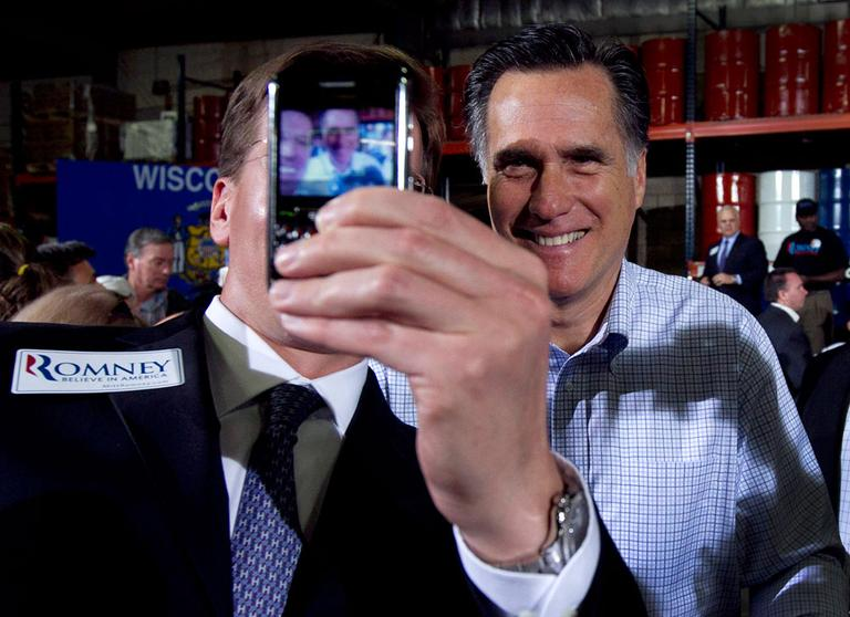 A member of the audience uses a mobile phone to record an image of himself with Republican presidential candidate, former Massachusetts Gov. Mitt Romney at the conclusion of a campaign event at an oil company in Milwaukee, Monday, April 2, 2012. (AP Photo/Steven Senne)