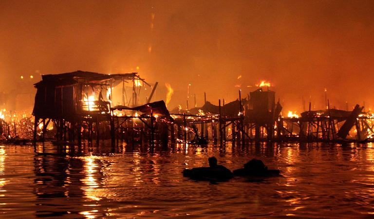 A man floats in the water with some of his belongings as his neighborhood is engulfed in fire Friday, May 11, 2012 in a slum area in Manila, Philippines. Officials say the fire that swept through a squatters' colony on Manila Bay's rim left two people missing and some 10,000 homeless. (AP Photo/Pat Roque)