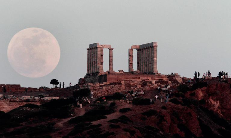 "A full moon rises behind the Temple of Poseidon in Cape Sounion, south east of Athens, Greece, while tourists watch, on Saturday, May 5, 2012. Saturday's event is a ""supermoon,"" the closest and therefore the biggest and brightest full moon of the year. (AP Photo/Dimitri Messinis)"
