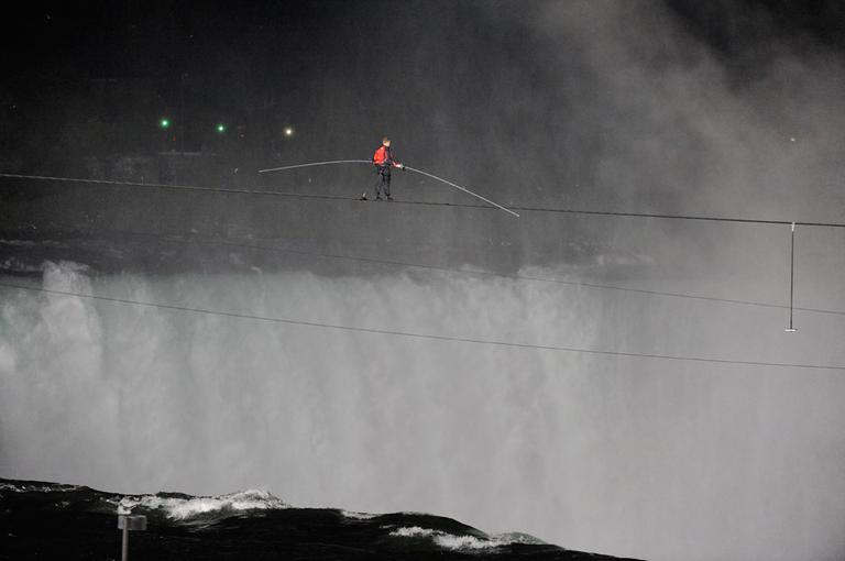 Nik Wallenda walks across NiagaraFalls on a tightrope as seen from NiagaraFalls, N.Y., Friday, June 15, 2012. Wallenda has finished his attempt to become the first person to walk on a tightrope 1,800 feet across the mist-fogged brink of roaring NiagaraFalls. (AP Photo/Gary Wiepert)