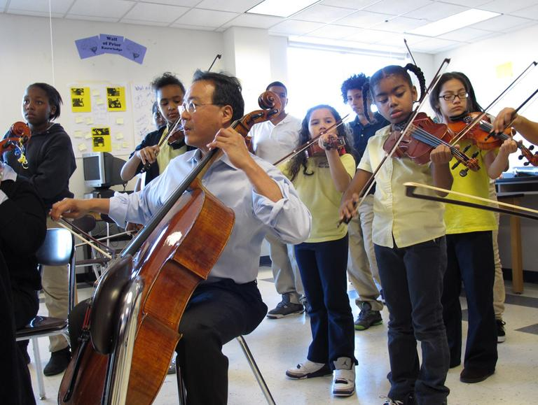 Yo-Yo Ma plays with orchestra students at the Orchard Gardens school Thursday. The famed cellist is part of a two-year musical exchange with students at the school, which has been designated as a Turnaround Arts school by the Obama administration. (Monica Brady-Myerov/WBUR)